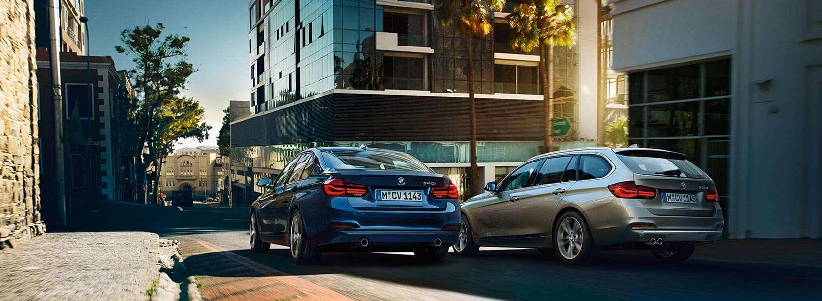 Aktualne oferty BMW zawsze zawiera ciekawe okazje. Dwa samochody BMW w przestrzeni miejskiej.